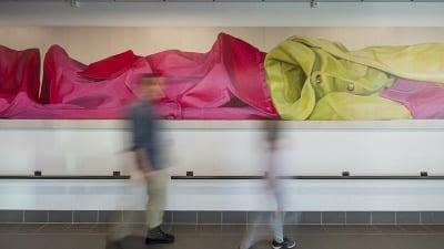 Två människor rör sig framför ett konstverk.
