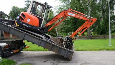 grävmaskin lastas av ett lastbilsflak.