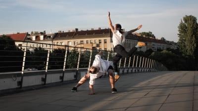 en kvinna och en man dansar på en bro