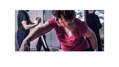 Kvinna gör svepande rörelse med ena armen