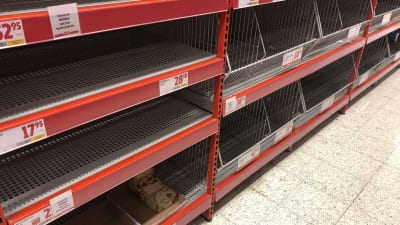 Tomma hyllor i livsmedelsbutik.