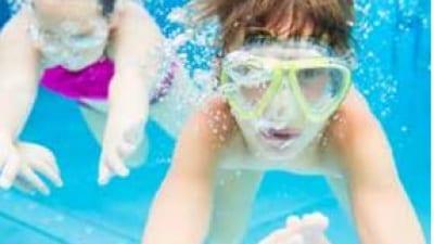 två barn simmar under vatten