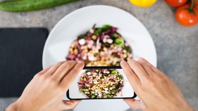 En mobiltelefon hålls i ovanför en tallrik mat.