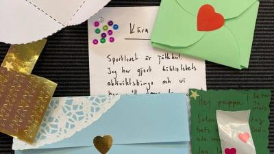 Olikfärgade brev med hjärtan på, brev med text samt en sax