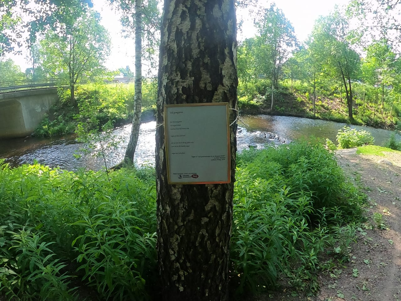 En vacker plats längs en å. På ett träd hänger en tavla med poesi.