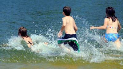 Barn badar i sjö.