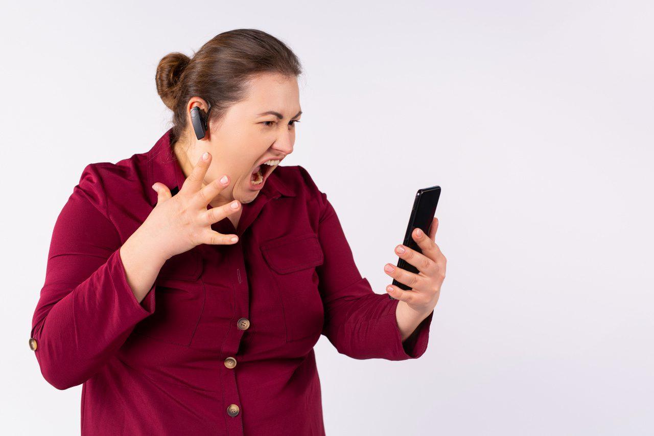 Kvinna håller i mobiltelefon och är upprörd för att den inte fungerar.