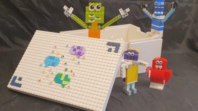 Fyra färgglada figurer i LEGO som står i och omkring en vit låda, dekorerad med chatt-rutor.